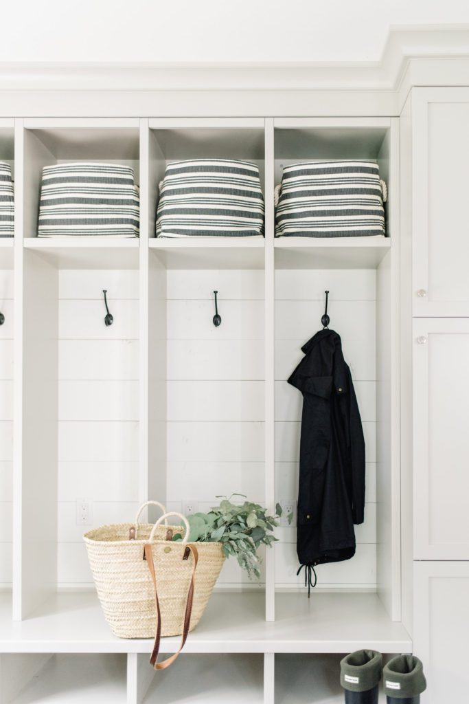 Open lockers with coat hooks and storage bins allow for quick access in this entryway