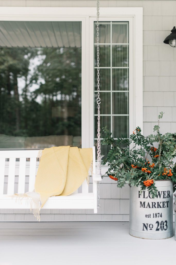 Foraged berry branches in galvanized tubs are a simple way to decorate the front porch for fall