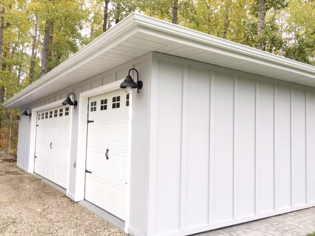 Grey board and batten siding and black gooseneck lights add modern farmhouse appeal to the detached garage.