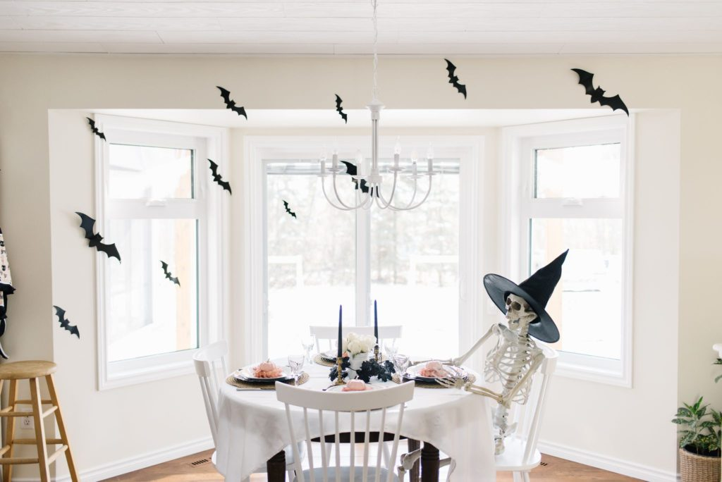 A skeleton has a seat at a Halloween tablescape