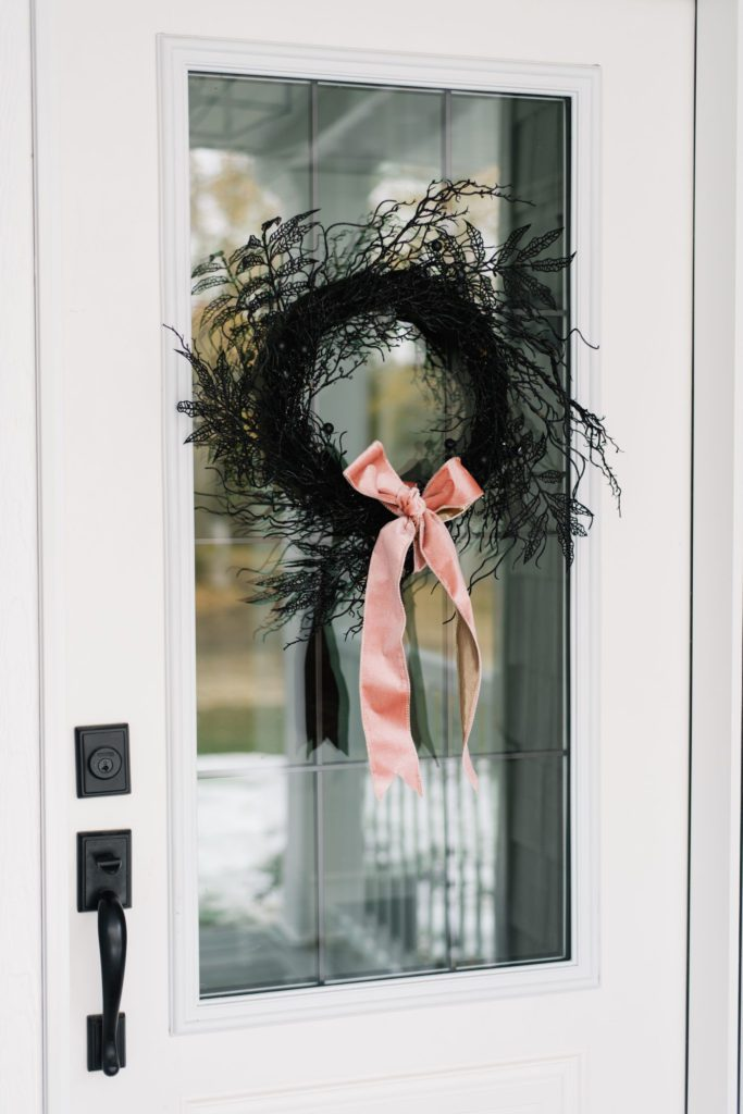 A simple black twig wreath looks luxe with a pink velvet bow for Halloween