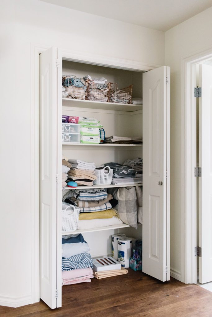 A well organized linen closet holds towels and toiletries