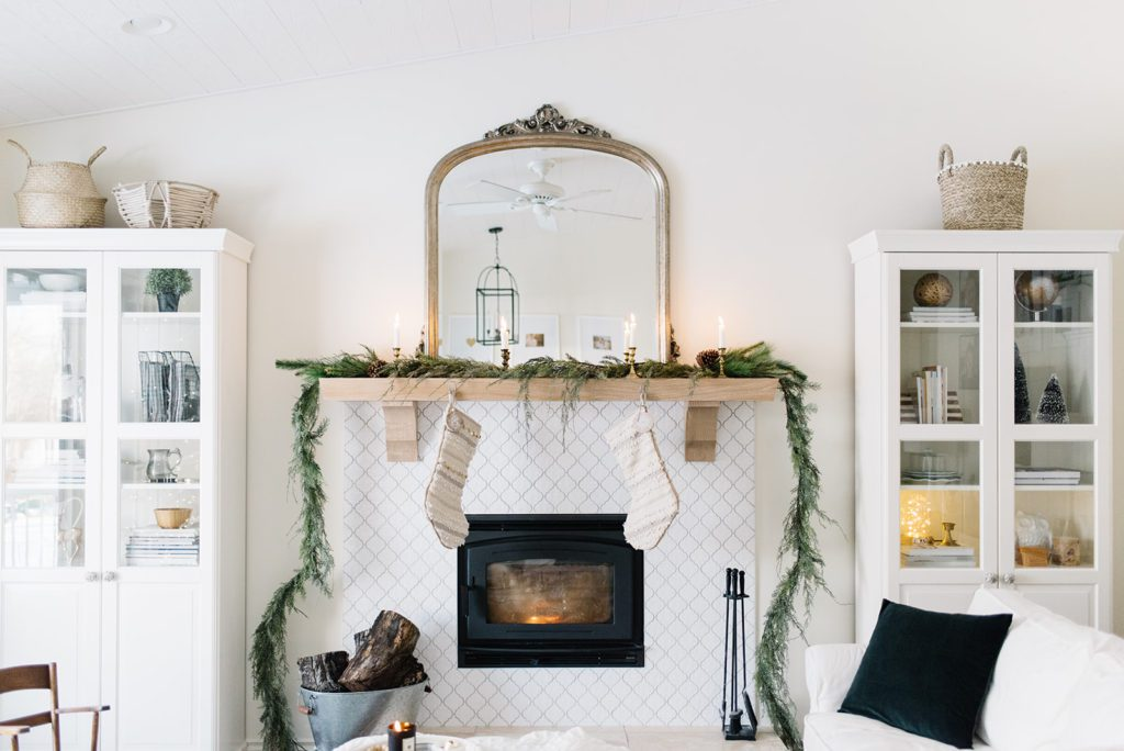 Simple Christmas mantle styling with cedar garland and vintage brass candlesticks