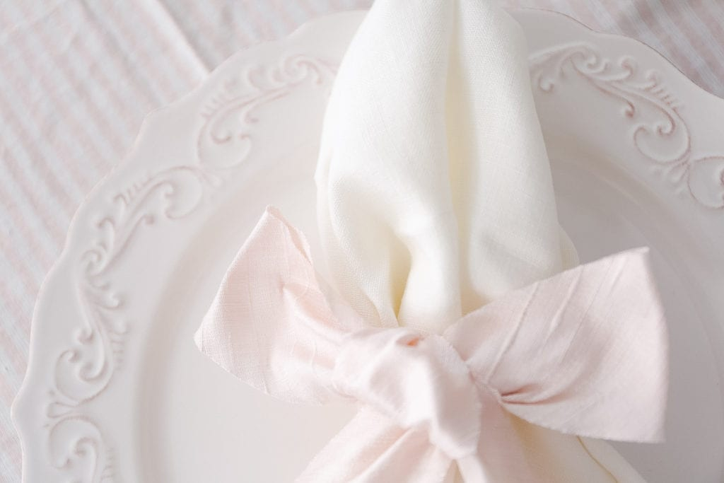 Linen napkins tied with pink silk ribbon are a simple idea for Valentine's Day Decorating