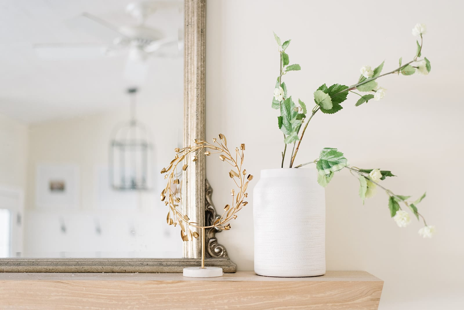 White vase with simple green and white flowers and a wreath adorn the mantle and don't distract from the pretty mirror at The Ginger Home