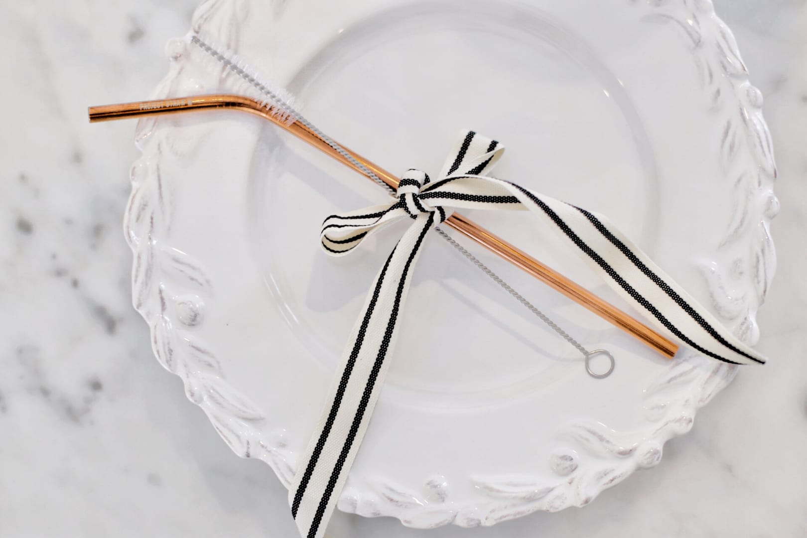 straw and brush tied with ribbon on plate