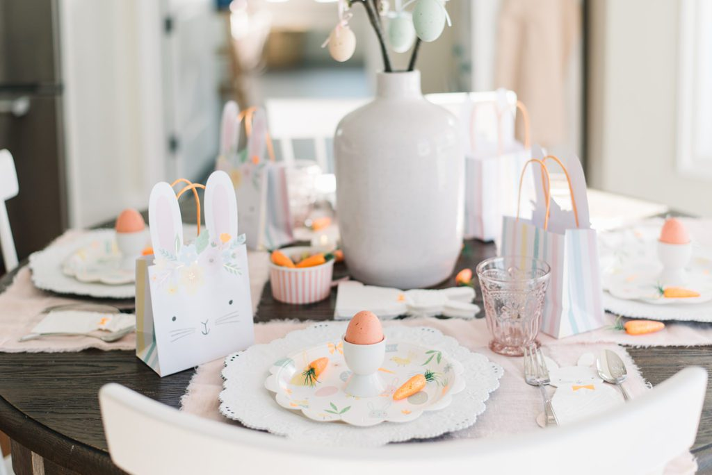 A pink and orange Easter Table setting for kids with bunny napkins egg cups and carrots