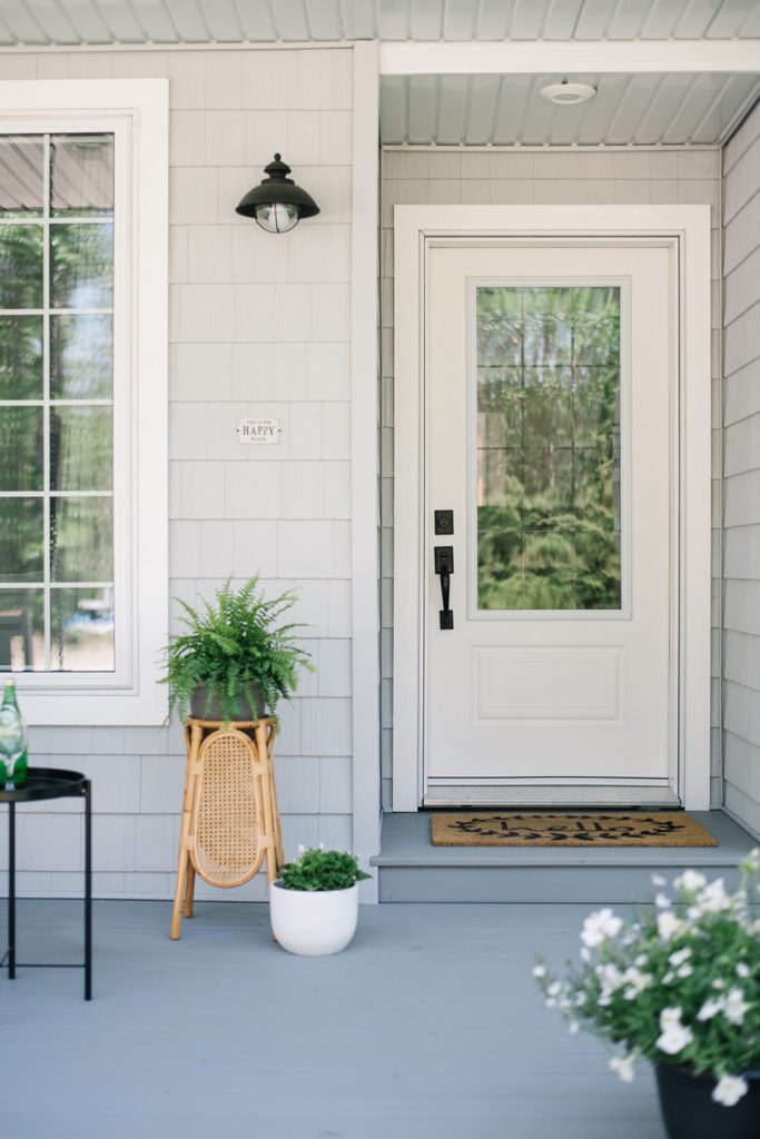 Summer porch decor - white front door, rattan plant stand