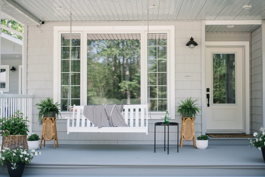 front porch with porch swing and greenery
