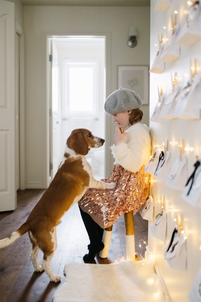Little girl and dog sitting infant of christmas lights