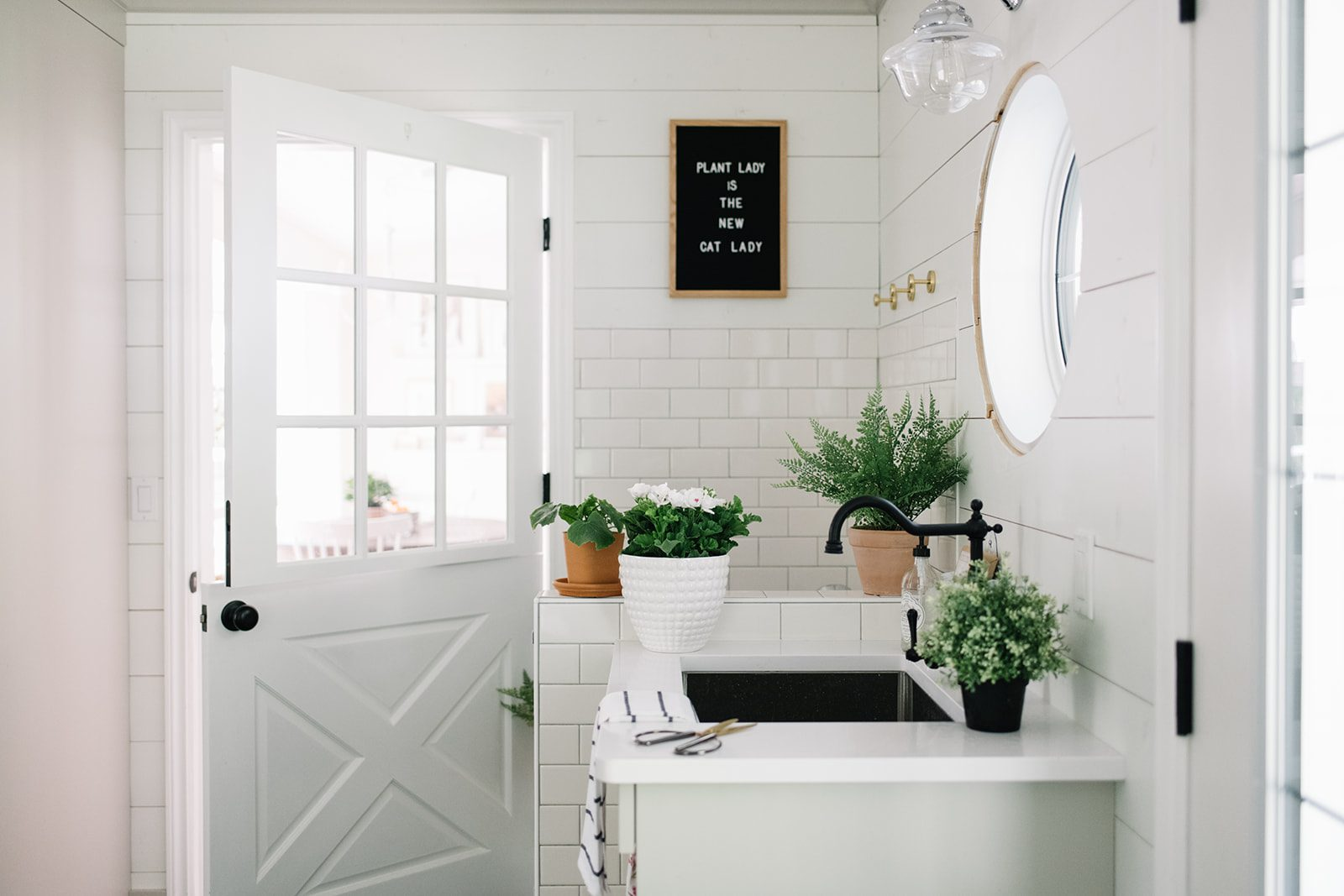 Watering houseplants in a neutral farmhouse mudroom