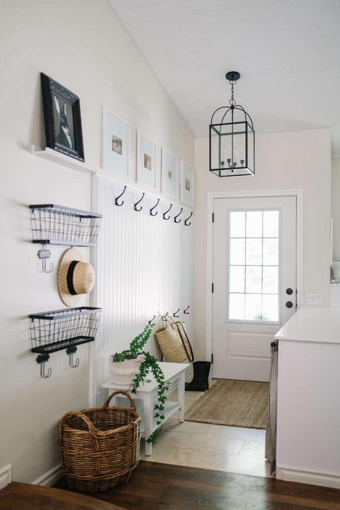 Small home entryway with hooks, baskets, and bench