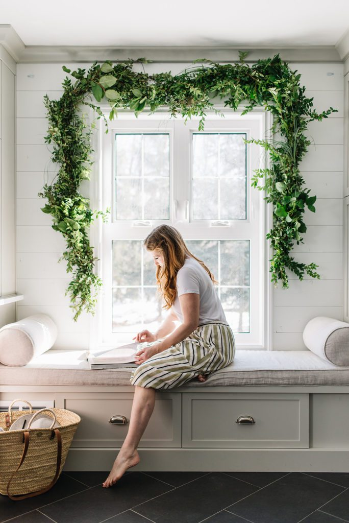 Spring greens - a garland draped over a mudroom window for Spring
