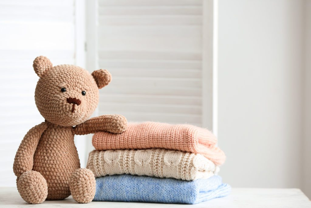 Teddy bear beside stack of sweaters
