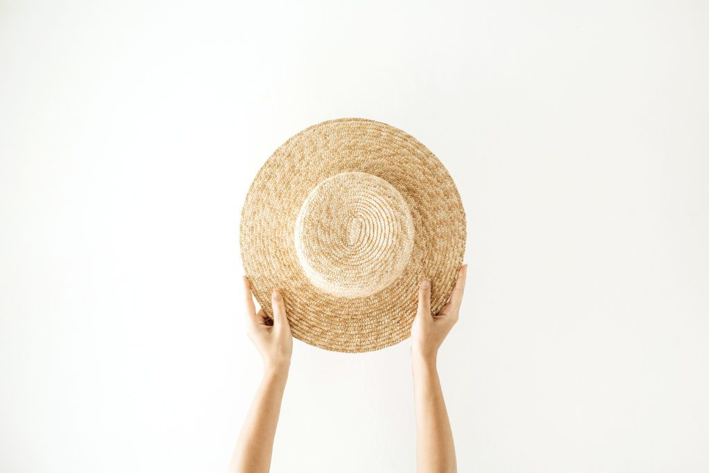 A simple straw hat held up with two hands.