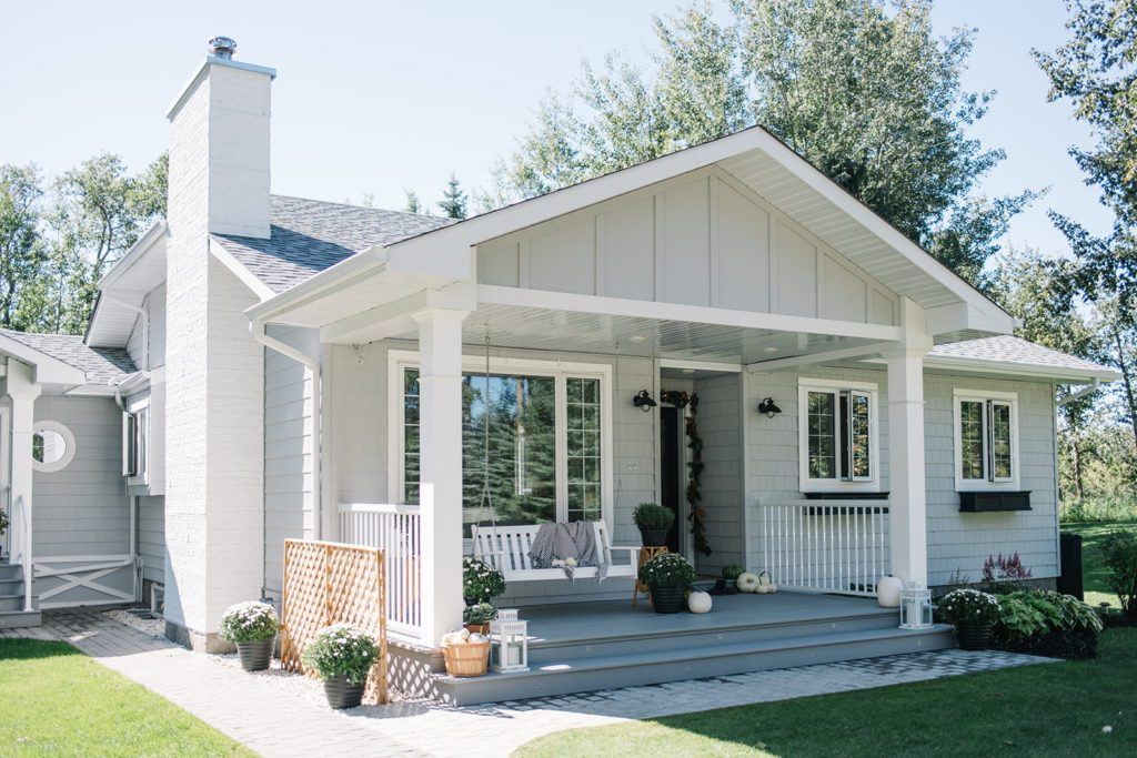 A modern farmhouse with grey siding, a porch swing and white accents.