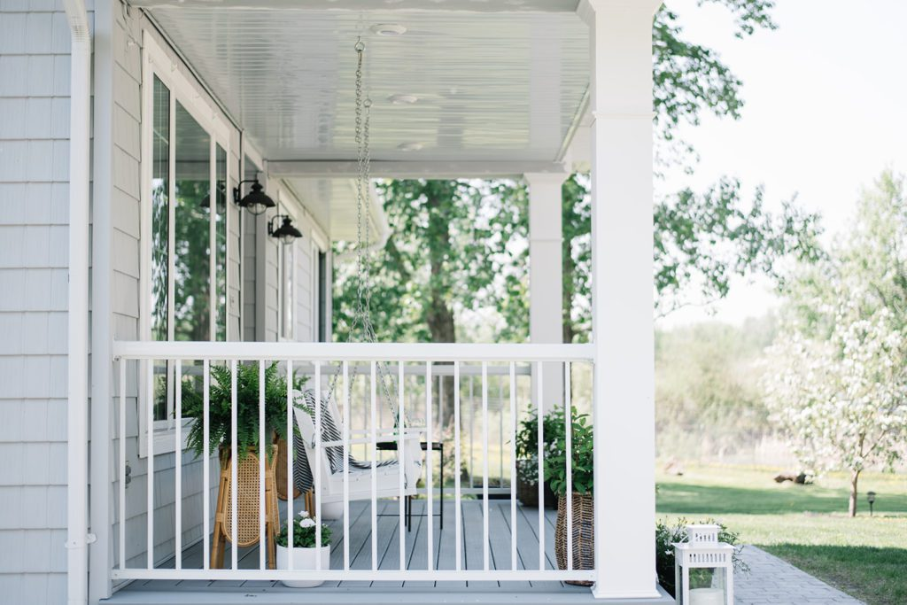 Modern Farmhouse front porch with white railings and porch swing overlooking green lawn and trees