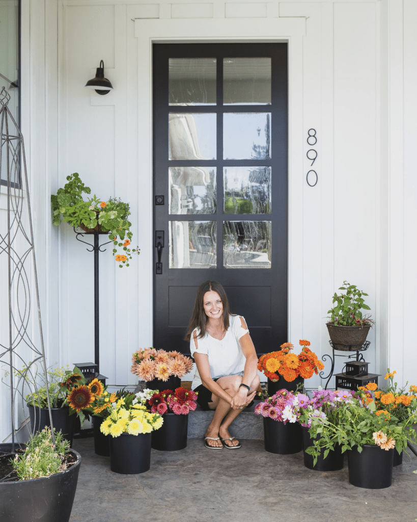 Jen from The Flowering Farmhouse on her front porch with buckets of flowers from her but flower garden.
