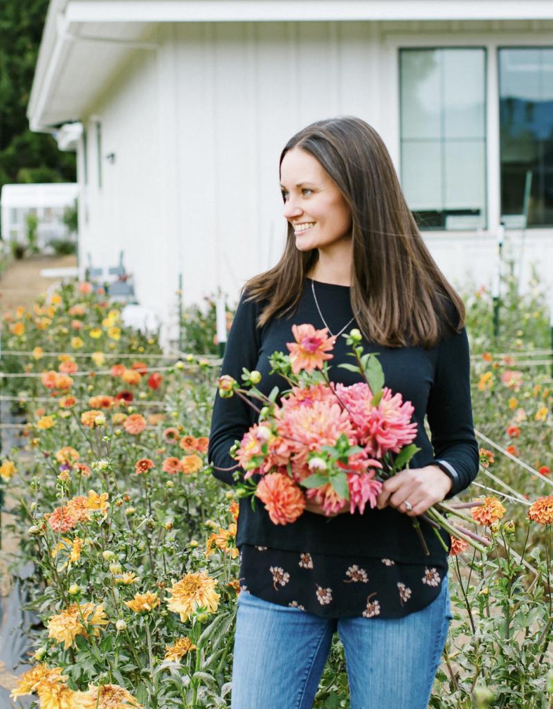 Woman in cut flower garden holding cut flowers