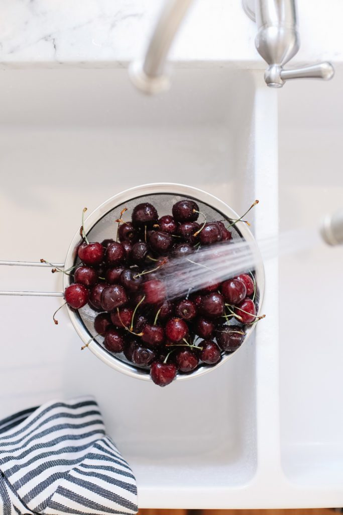 Cherries being washed in sink