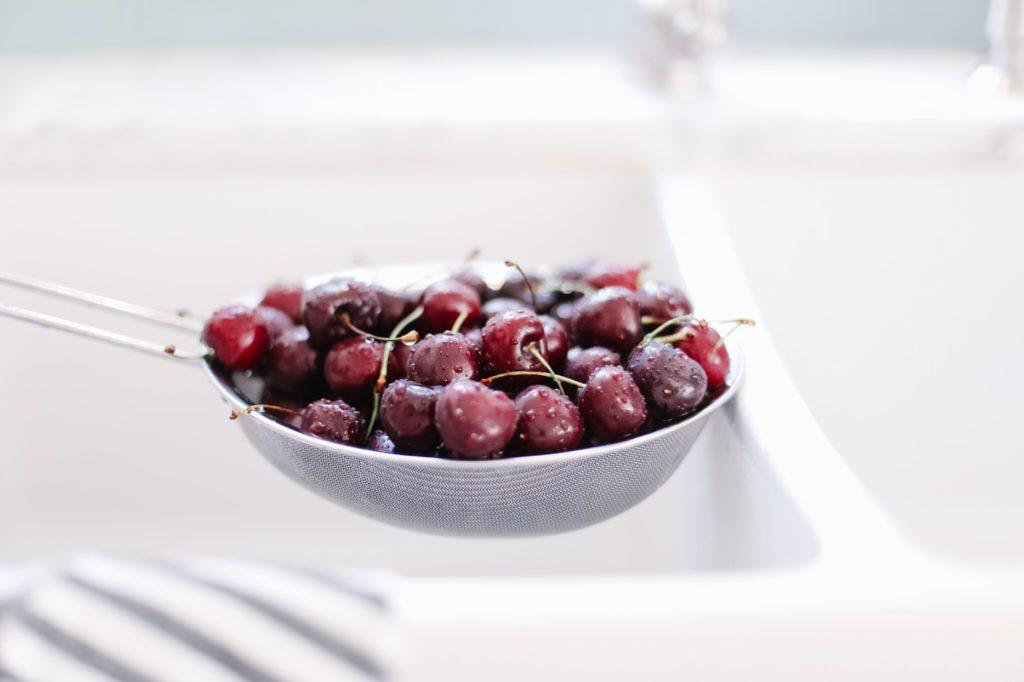 fresh cherries in a strainer
