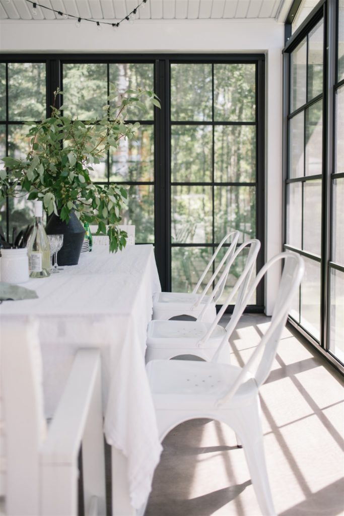 simple white table and chairs with greens in 3 season room
