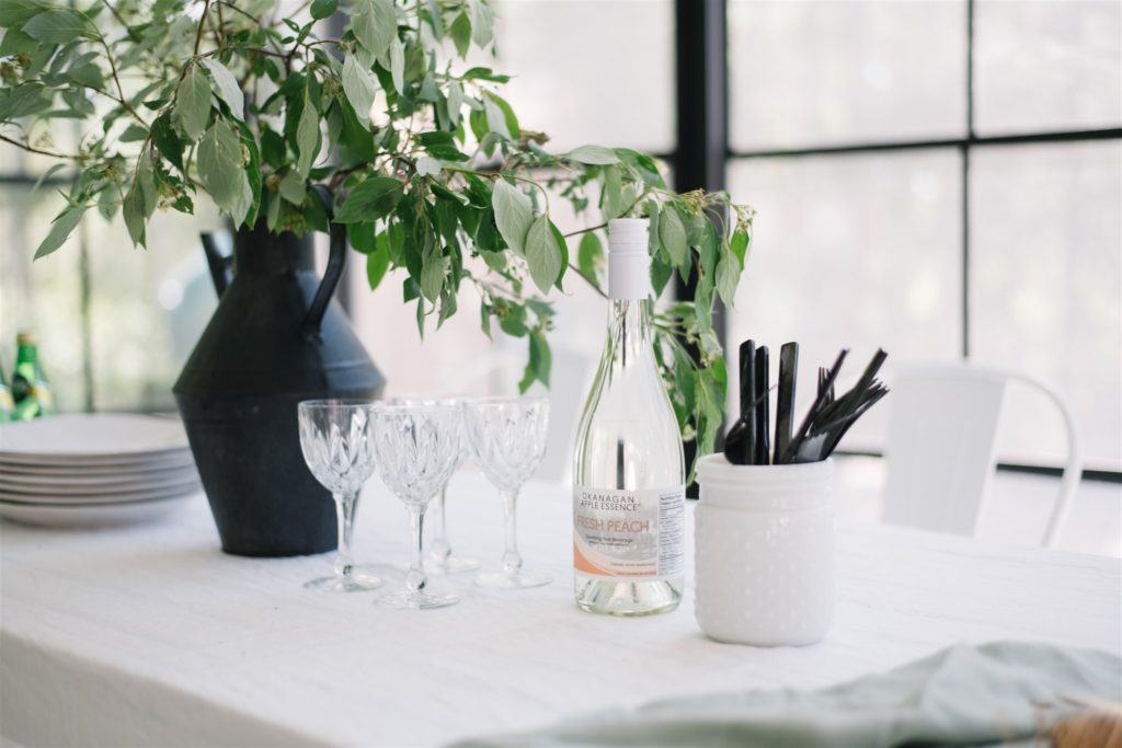 simple summer table setting with greens and crystal glasses