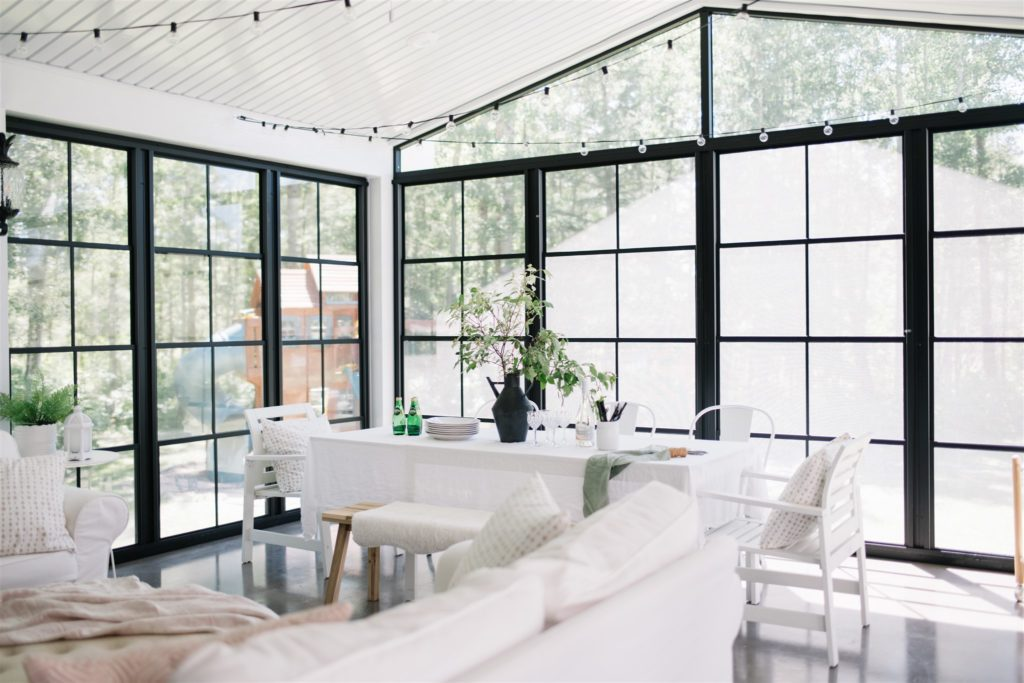 summer dining table in screen room with string lights