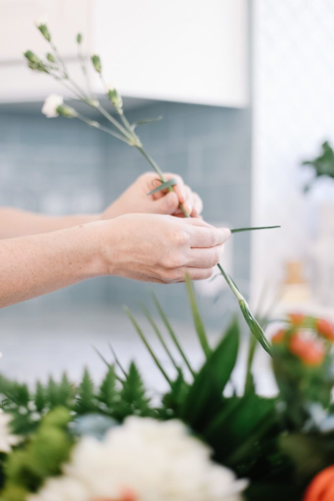 Stripping leaves off the stems off cut flowers