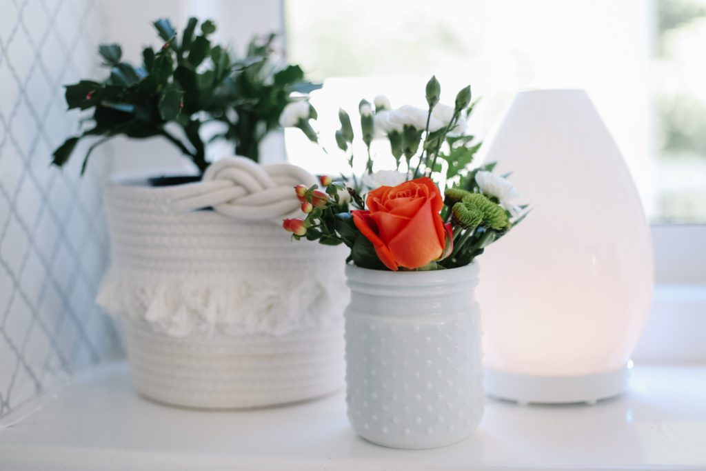 Small flower arrangement beside plant and diffuser