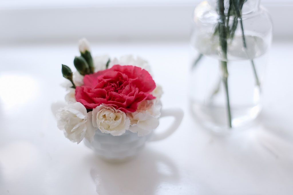 small flower arrangement with pink and white flowers in sugar bowl