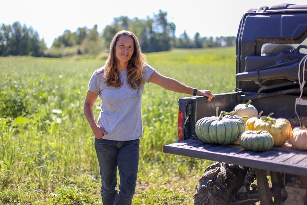 Woman stands next to truck full of pumpkins