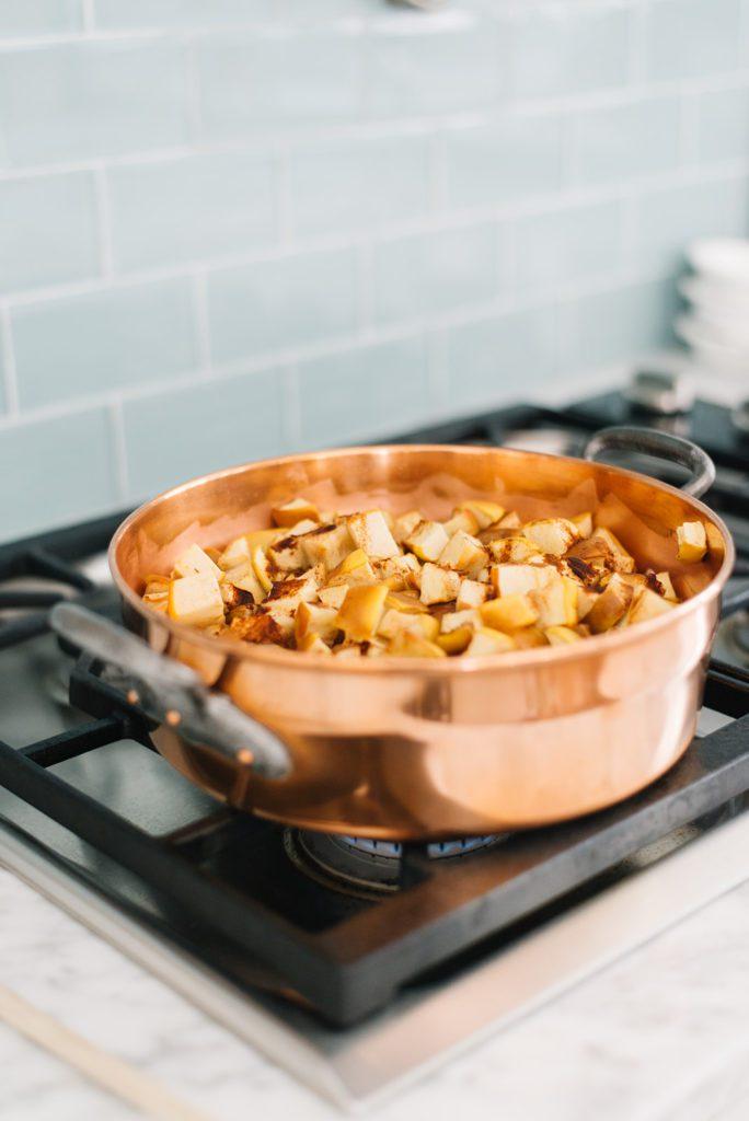 Copper jam pan full of applesauce on the stove.