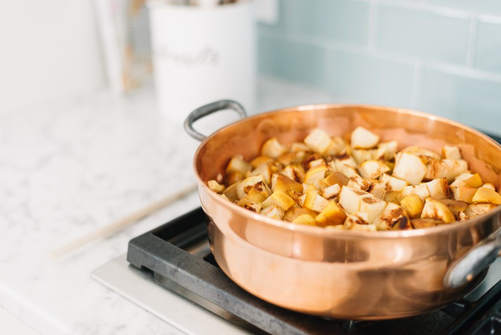 Copper pot full of applesauce on stove