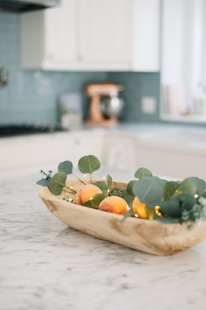 Peaches in dough bowl on kitchen island with twinkle lights