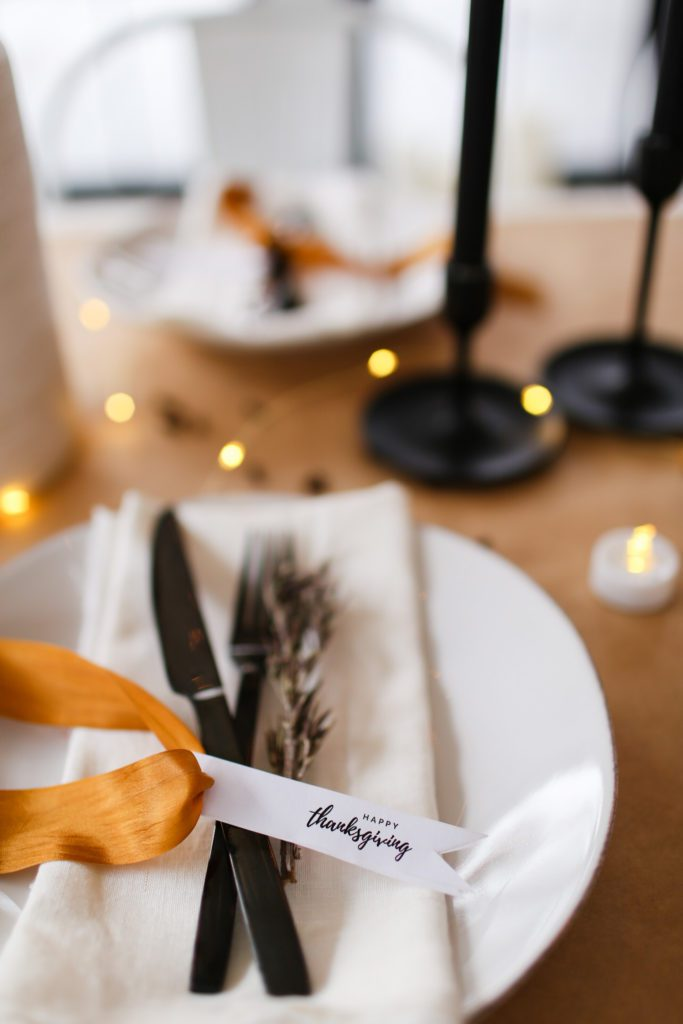 A place setting with white plate, black cutlery, gold ribbon and printable Happy Thanksgiving tag!