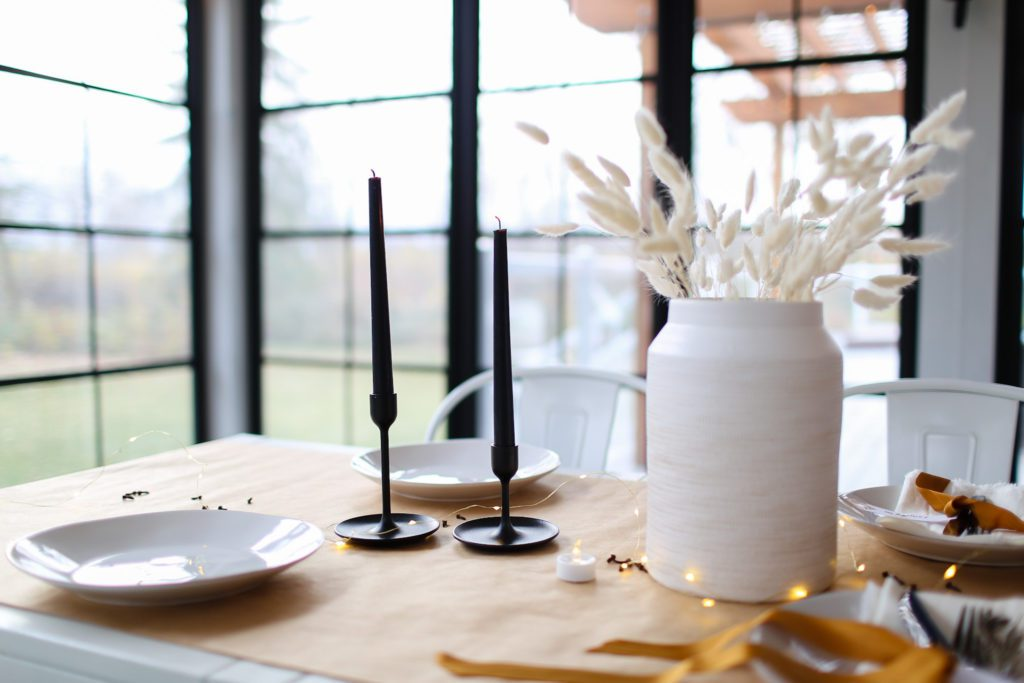 Simple table set with a white vase full of grasses, black candlesticks and brown kraft paper