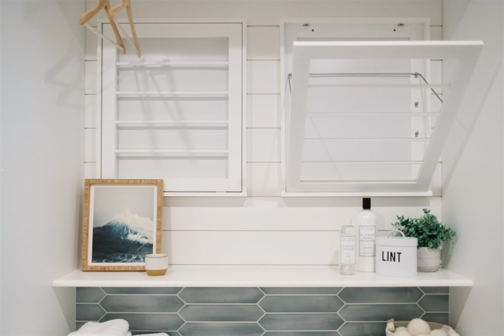Wall mounted drying racks in a laundry room.