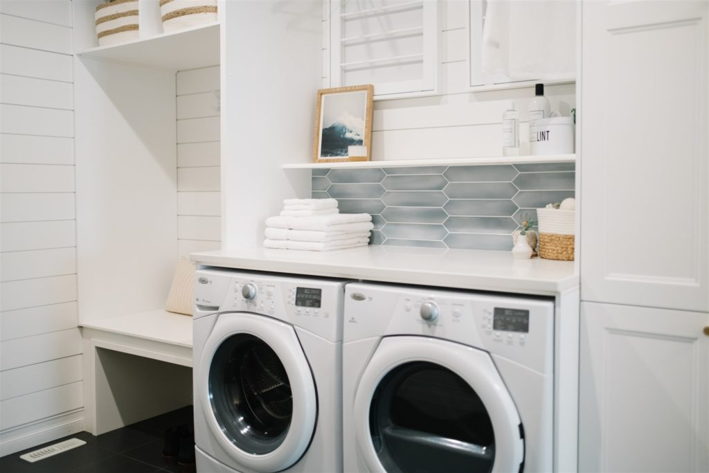 Laundry room with white cabinetry and shiplap walls