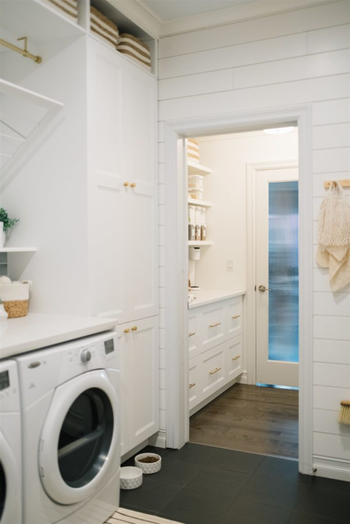 Laundry room and pantry spaces with white cabinets and dark floors