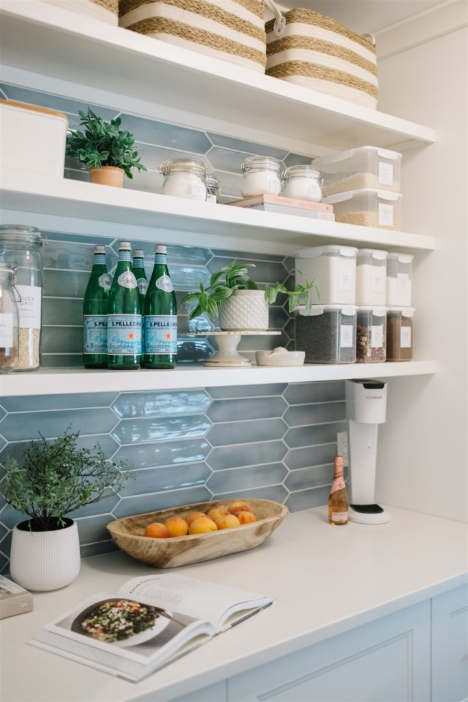 Organized and styled white pantry shelves with blue tile background.