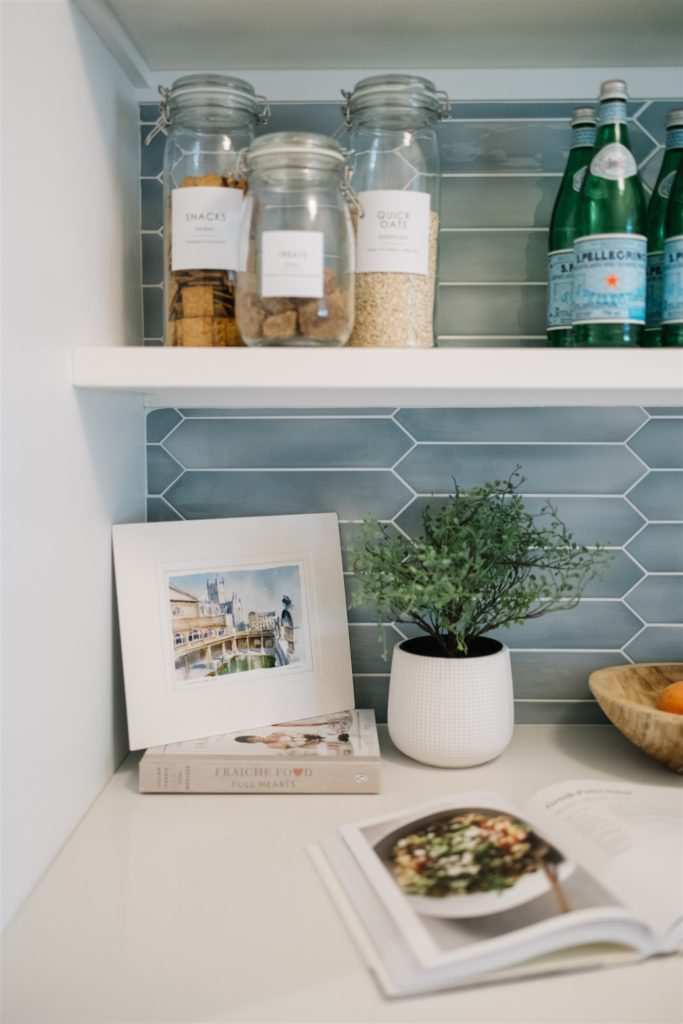 Styled pantry shelves with art, containers, plants and bottles