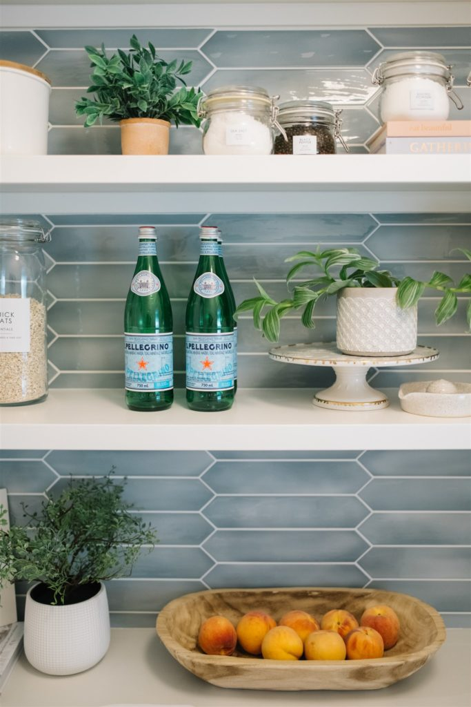 Pantry shelves full of bottles, fruit, plants and containers