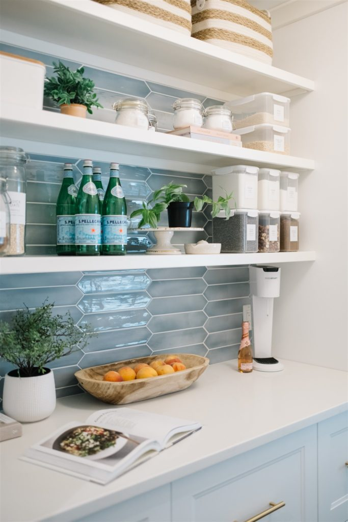 A pretty pantry with containers, a bowl of fruit and blue tile with white shelves