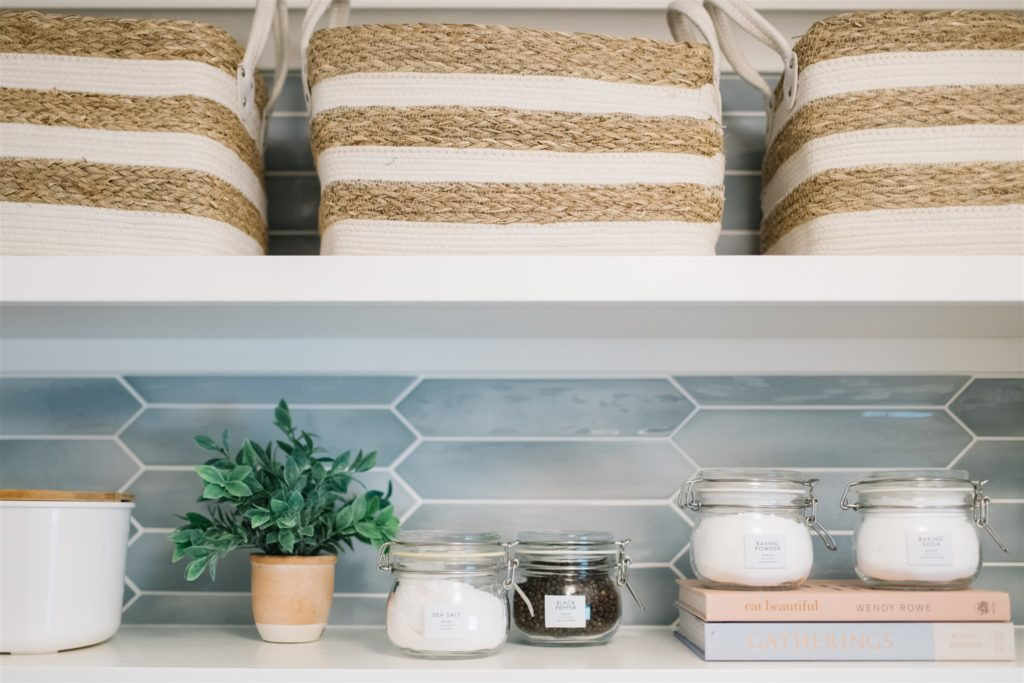 Pretty striped baskets, jars and cookbooks on white pantry shelves.