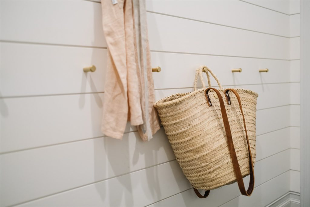 Mudroom wall with hooks and a french market tote and apron hanging.