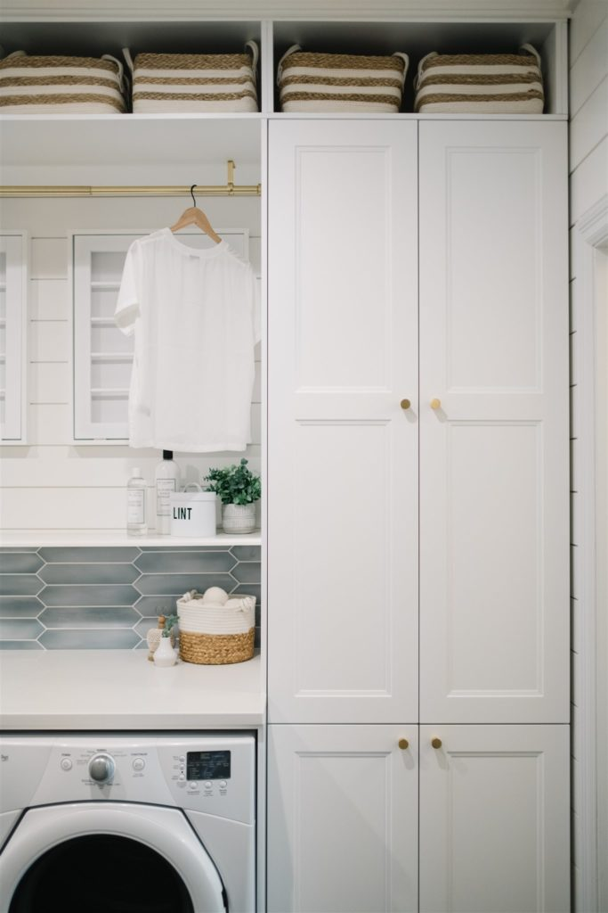 Pretty laundry room with white cabinetry and blue tile.