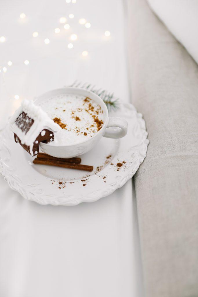 Cute mini gingerbread house on a mug in bed.