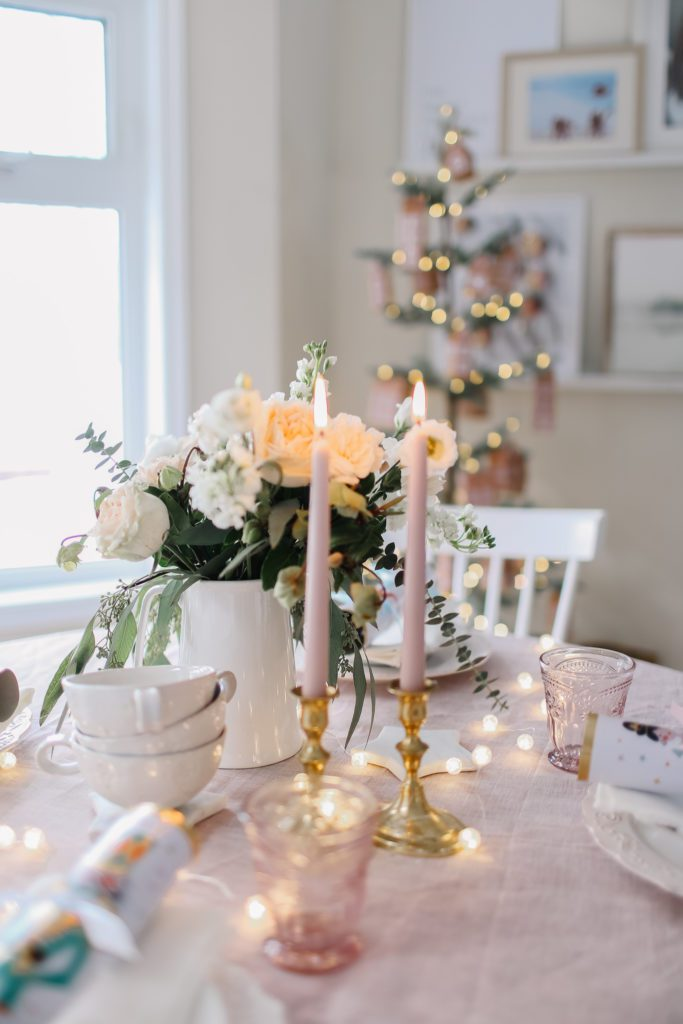 Christmas brunch table with pink table cloth and candles and nutcracker christmas crackers
