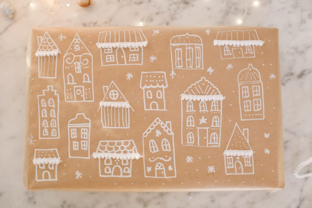 Gift wrapped in kraft brown paper with hand drawn houses in chalk marker